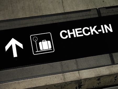 Airport sign pointing to check-in area, placed on exposed concrete beam. photo