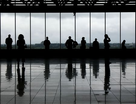 delay: Silhouetted people against the windows of an airport observation deck. The greyish floor and clouded day gives it a very monochrome aspect.