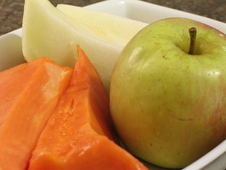 Closeup view of melon and papaya slices and an apple on a white plate Stock Photo