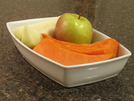 Closeup view of melon and papaya slices and an apple in a white plate on a marble counter