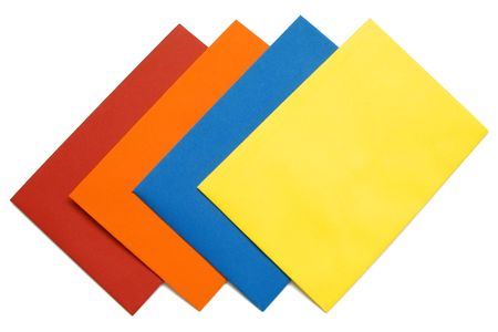 A series of four bright envelopes (red, blue, yellow and orange), orderly arranged, isolated on white with natural shadows. Stock Photo