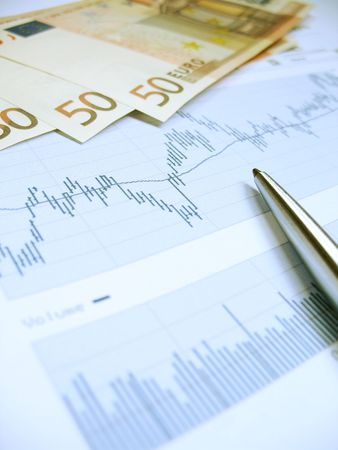Stock market charts for investor analysis, with Euro $50 bills and pen, using selective focus on graph and pen. Stock Photo