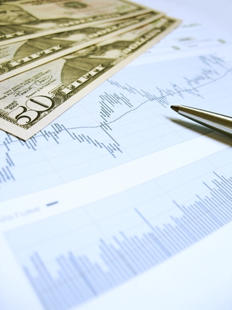 Stock market charts for investor analysis, with US$50 bills and pen, using selective focus on one banknote and graph. Stock Photo