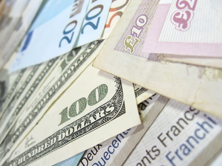 Close-up view of banknotes of various currencies (US dollars, British pounds, Euros and Swiss Francs), with selective focus.