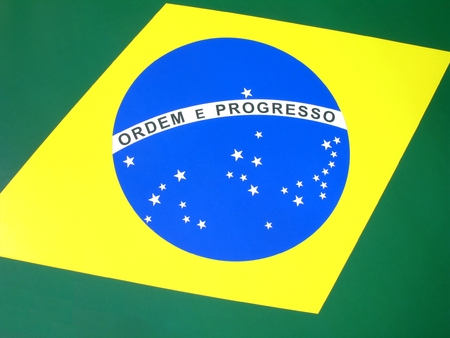 Close-up view of the national flag of Brazil.  The Brazilian flag is composed of a yellow rhombus on a green rectangle, inside which there is a blue circle with 27 stars representing each of the country states and the
