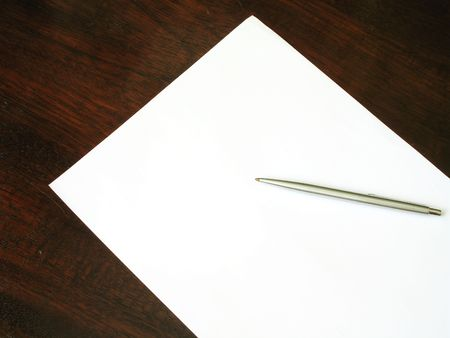 A white sheet of paper with pen on a wood desk, viewed from above.