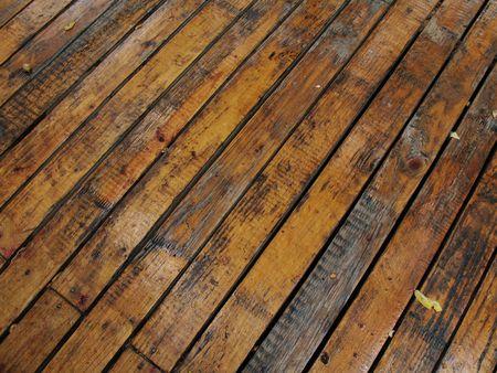 Ponte pavimenti in legno tavole, bagnato dopo la pioggia e mostrati in diagonale.