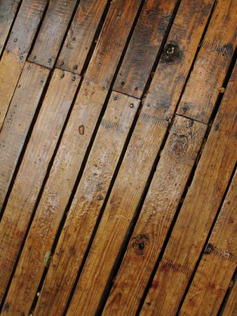 Deck flooring made of wood planks, wet after the rain and shown diagonally. Stock Photo