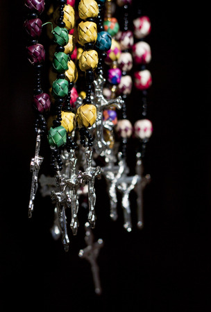 Rosaries and crosses hanging in front of a black background