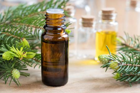 A bottle of fir essential oil with fir branches