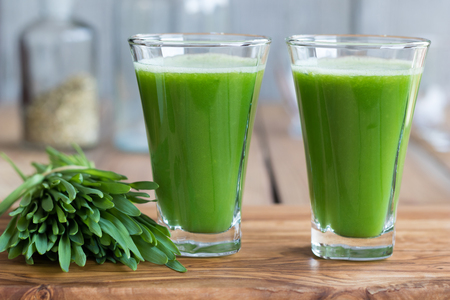 Two green barley grass shots with blades of young barley on a wooden background Stock Photo