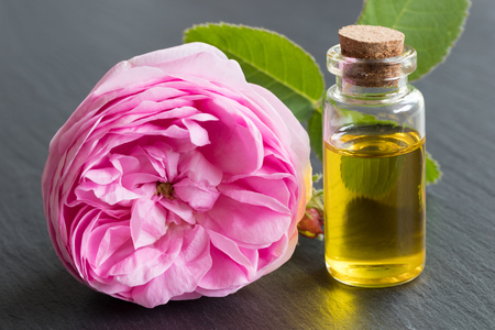 Rose essential oil: a bottle of oil with a rose flower on a black background Archivio Fotografico