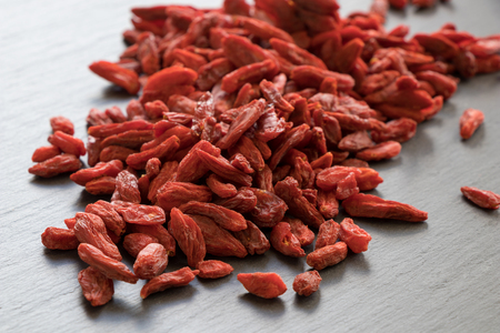 close up food: A pile of dried goji berries on a stone background.