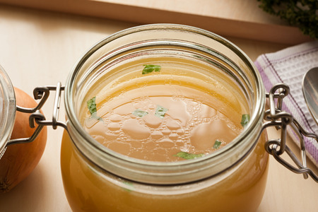 Bone broth made from chicken in a glass jar on a wooden background