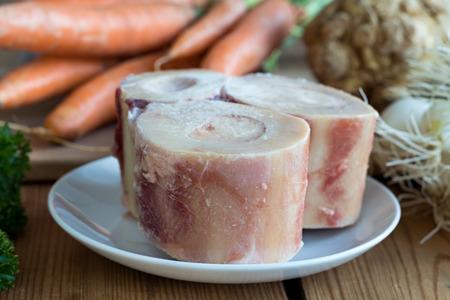 Ingrédients pour la fabrication d'un bouillon d'os de boeuf - os de moelle, carottes, oignons, céleri-rave