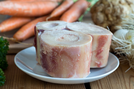 Ingredients for making a beef bone broth - marrow bones, carrots, onions, celery root