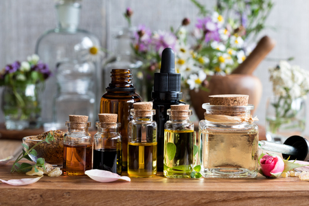 Selection of essential oils, with herbs and flowers in the background