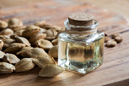 A bottle of apricot kernel oil with apricot kernels on a wooden background Archivio Fotografico