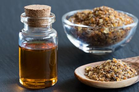 A bottle of myrrh essential oil with myrrh resin on a dark background Stock fotó