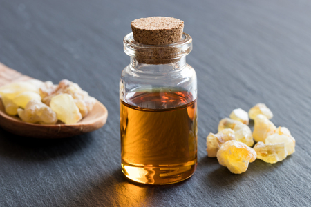 A bottle of frankincense essential oil with frankincense resin on a dark background