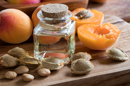 A bottle of apricot kernel oil with apricot kernels and ripe apricots on a wooden background Archivio Fotografico