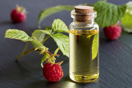 A bottle of raspberry seed oil with raspberries on a dark background Stock fotó