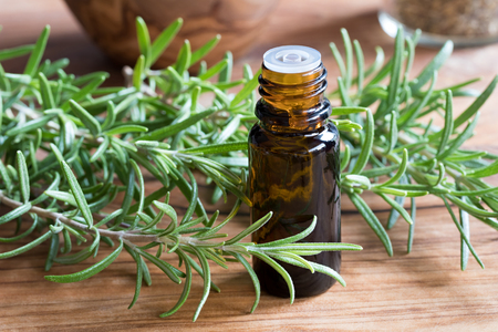A bottle of rosemary essential oil with fresh rosemary twigs on a wooden table