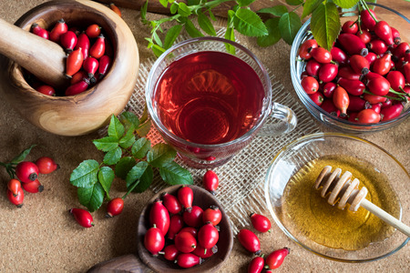 A cup of rose hip tea on a table, with fresh rose hips in the background