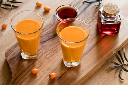 Two glasses of sea buckthorn juice, with sea buckthorn oil and berries in the background