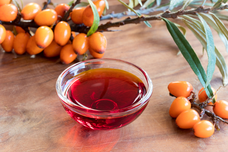 Sea buckthorn oil in a glass bowl on a wooden table, with sea buckthorn berries and leaves in the background