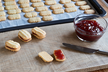 Christmas cookies taken out of the oven are being filled with strawberry jam