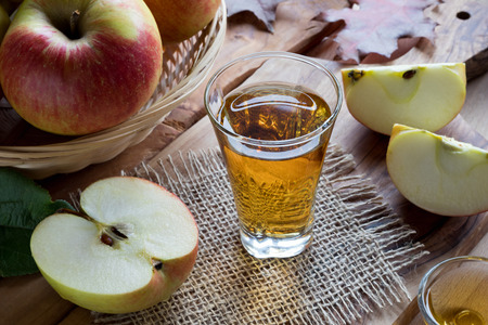 Apple cider vinegar in a glass on a wooden table, with apples in the background