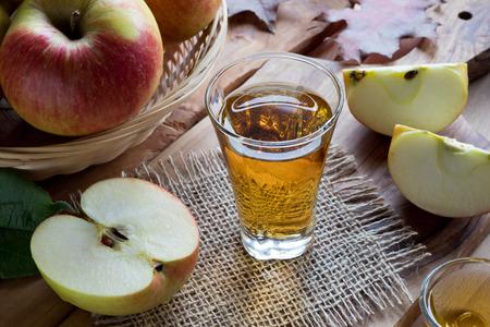 Apfelessig in einem Glas auf einem Holztisch, mit Äpfeln im Hintergrund Standard-Bild