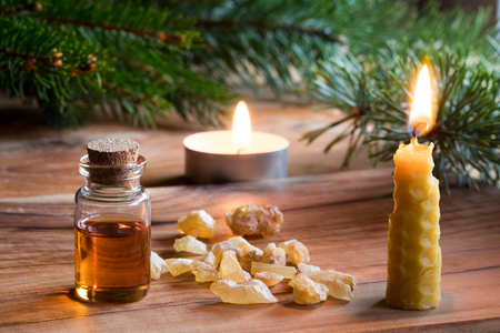 A bottle of frankincense essential oil with frankincense resin crystals, a candle made from beeswax, and spruce and pine branches in the background. Christmas styled.