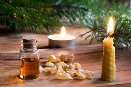 Une bouteille d'huile essentielle d'encens avec des cristaux de résine d'encens, une bougie faite de cire d'abeille, et des branches d'épinette et de pin en arrière-plan. Noël de style.