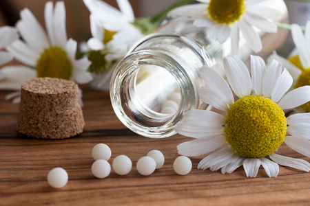 A bottle of homeopathic globules with chamomile flowers on a table Stock Photo