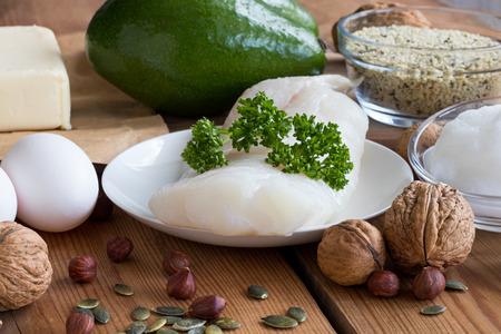 Healthy fats - wild caught fish, avocado, butter, eggs, hemp seeds, walnuts, hazelnuts, pumpkin seeds, coconut oil Stock Photo