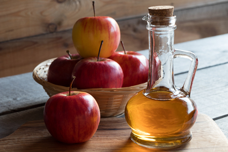 A bottle of apple cider vinegar with apples in the background Фото со стока