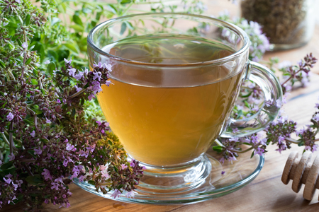 A cup of Breckland thyme (thymus serpyllum) tea, with fresh blooming Breckland thyme on a wooden background Stockfoto