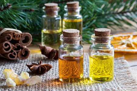 Selection of essential oils with star anise, cinnamon, frankincense resin, dried orange slice and pine branches in the background