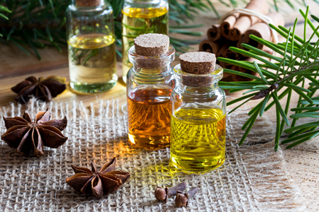Selection of essential oils with star anise, clove, cinnamon sticks and fir branches
