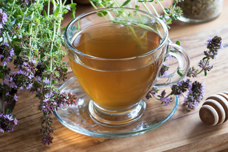 A cup of creeping thyme (thymus serpyllum) tea, with blooming creeping thyme twigs on a wooden background