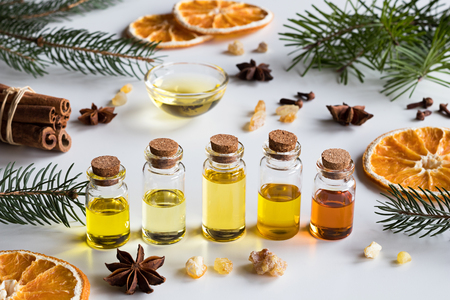 Christmas selection of essential oils and spices on white background: bottles of essential oil, spruce, fir, frankincense resin, star anise, cinnamon, clove, dried orange. Stockfoto
