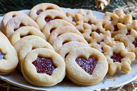 Traditional Linzer Christmas cookies filled with strawberry jam and dusted with sugar, arranged on a plate