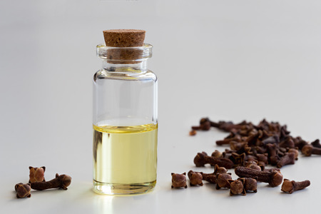 A transparent bottle of clove essential oil with dried cloves on a white background