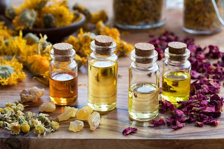목조 배경에 말린 된 장미 꽃잎, 카모마일, 금 송 화와 유향 수지와 에센셜 오일의 병 스톡 콘텐츠