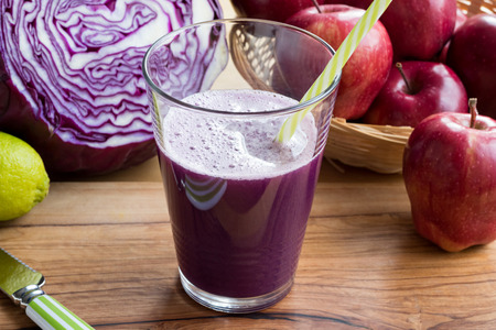 Purple cabbage juice in a glass, with cabbage and apples in the background