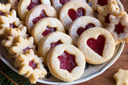 Linzer Christmas cookies filled with strawberry jam and dusted with sugar, arranged on a plate Stock Photo