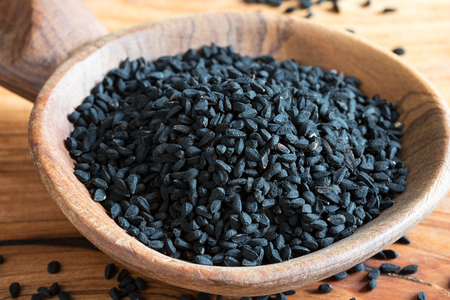 Black cumin seeds on a wooden background