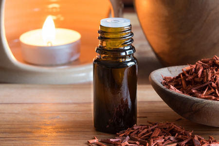 A bottle of sandalwood essential oil with sandalwood and copy space, with an aroma lamp in the background
